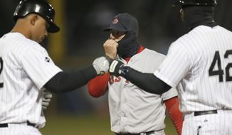 CORRECTS TO SIXTH INNING, INSTEAD OF FOURTH - Boston Red Sox first baseman Mike Napoli, center, warms his hand through his balaclava as Chicago White Sox's Jose Abreu, left, reaches first and first base coach Daryl Boston during the sixth inning of a baseball game Tuesday, April 15, 2014, in Chicago. Temperatures remained in the mid-30s for the game. (AP Photo/Charles Rex Arbogast)