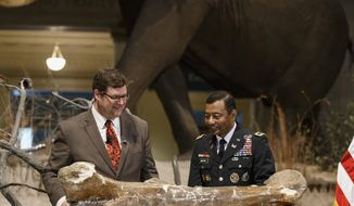 Smithsonian National Museum of Natural History Director Kirk Johnson, left, and Lt. Gen. Thomas Bostick, commanding general of the Army Corps of Engineers, unveil the fossilized bones of a Tyrannosaurus rex during a ceremony at the museum in Washington, Tuesday, April 15, 2014. The Tyrannosaurus rex is joining the dinosaur fossil collection on the National Mall on Tuesday after a more than 2,000-mile journey from Montana.  For the first time since its dinosaur hall opened in 1911, the Smithsonian's National Museum of Natural History will have a nearly complete T. rex skeleton. FedEx is delivering the dinosaur bones in a truck carrying 16 carefully packed crates.  (AP Photo/J. Scott Applewhite)