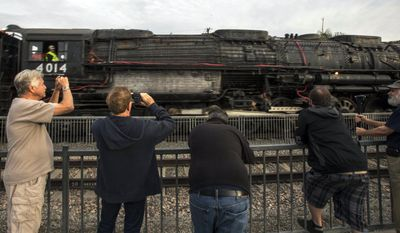 File - In this Jan. 26, 2014 file photo, spectators snap pictures of Union Pacific Big Boy No. 4014 on, in Covina, Calif., after the locomotive was moved from the RailGiants Train Museum, where it was on display. The locomotive was to head for Colton over the next several weeks before No. 4014 is towed to Union Pacific's Heritage Fleet Operations headquarters in Cheyenne, Wyo. (AP Photo/Ringo H.W. Chiu, file)