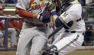 Milwaukee Brewers catcher Jonathan Lucroy, right, tags out St. Louis Cardinals' Jhonny Peralta at home during the fourth inning of the MLB National League baseball game Tuesday, April 15, 2014, in Milwaukee. Peralta tried to score from second on a hit by Peter Bourjos. (AP Photo/Morry Gash)