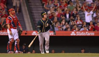 Oakland Athletics' John Jaso, right, hits a two-run home run as Los Angeles Angels catcher Hank Conger looks on during the ninth inning of a baseball game, Monday, April 14, 2014, in Anaheim.  (AP Photo/Mark J. Terrill)