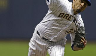 Milwaukee Brewers starting pitcher Matt Garza throws to the St. Louis Cardinals during the first inning of  the MLB National League baseball game Monday, April 14, 2014, in Milwaukee. (AP Photo/Jeffrey Phelps)