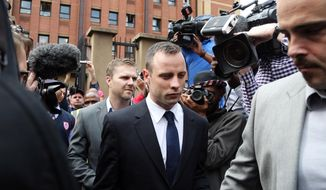 Oscar Pistorius, center, leaves the high court in Pretoria, South Africa, Tuesday, April 15, 2014. Pistorius is charged with murder for the shooting death of his girlfriend, Reeva Steenkamp, on Valentines Day in 2013. (AP Photo/Themba Hadebe)