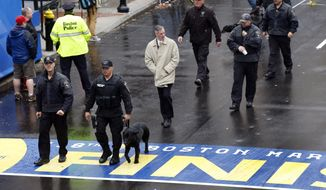 Security personnel walk across the Boston Marathon finish line prior to a remembrance ceremony for family members and survivors of the 2013 Boston Marathon bombing, on Boylston Street in Boston, Tuesday, April 15, 2014. (AP Photo/Elise Amendola)