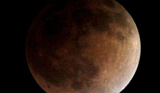As the moon completely crosses the earth's shadow, the first of four total lunar eclipses, called the Blood Moon, occur in Whittier, Ca., USA on Tuesday, April 15, 2014. (AP Photo/Nick Ut )