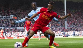 Liverpool's Raheem Sterling, right, keeps the ball from Manchester City's Yaya Toure during their English Premier League soccer match at Anfield Stadium, Liverpool, England, Sunday April 13, 2014. (AP Photo/Jon Super)