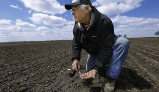 Central Illinois corn and soybean farmer Garry Niemeyer inspects the soil temperature and the sprouting of corn seeds he planted earlier as a test Tuesday, April 15, 2014, in Auburn, Ill. Farmers eager to fire up the combines and get their corn crops in the ground are being foiled by an uncooperative spring after a long winter. The U.S. Department of Agriculture expects farmers to now launch into full-scale planting at the end of this month, later than usual. (AP Photo/Seth Perlman)