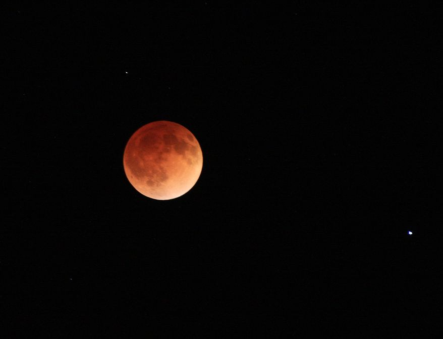 The moon glows a red hue during a total lunar eclipse Tuesday, April 15, 2014, as seen from the Billings, Mont., area. Tuesday's eclipse is the first of four total lunar eclipses that will take place between 2014 to 2015. (AP Photo/The Billings Gazette, Bob Zellar)