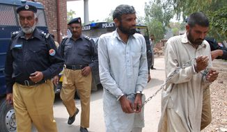 Pakistani police officers escort Farman Ali, right, and Arif Ali, two brothers suspected of cannibalism to a local court in Sargodha, Pakistan, Tuesday, April 15, 2014. Police raided their house in central Pakistan Monday morning after neighbors complained of a horrible stench. Police officer Zafar Iqba said the men were previously jailed for two years on charges of digging up bodies, cooking and eating them in 2011. (AP Photo/M.I. Haq)