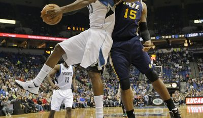 Minnesota Timberwolves center Ronny Turiaf, left, of France, pulls down a rebound against Utah Jazz center Derrick Favors (15) during the second quarter of an NBA basketball game in Minneapolis, Wednesday, April 16, 2014. (AP Photo/Ann Heisenfelt)