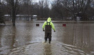 Neil Hock, 44, wades through floodwater in Sanford, Mich., Tuesday, April 15, 2014. Several Michigan rivers are over their banks after three days of storms dropped as much of 5.5 inches of rain, forcing some flood plain residents from their homes. Hock evacuated April 14 after the waters flooded his home.(AP Photo/The Saginaw News, Tim Goessman) ALL LOCAL TV OUT; LOCAL TV INTERNET OUT
