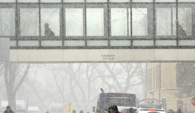 Heavy snow started to fall as students at St. Cloud State University, St. Cloud, Minn., use the skyway and the street between the Robert H. Wick Science Building and Brown Hall the get around between classes, Wednesday, April 16, 2014. (AP Photo/St. Cloud Times, Jason Wachter)