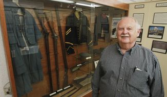 "In this March 26, 2014 photo, Tom Snyder, a retired Air Force historian, stands next to a case of authentic Civil War items on exhibit at the Mascoutah Heritage Museum in Mascoutah, Ill. Snyder helped set up the exhibit that honors the 464 Mascoutah men who fought in the Civil War, including their families, friends and neighbors they left behind. Snyder also wrote a 203-page book, ""Mascoutah, Illinois, in the Civil War."" (AP Photo/Belleville News-Democrat, Derik Holtmann)"