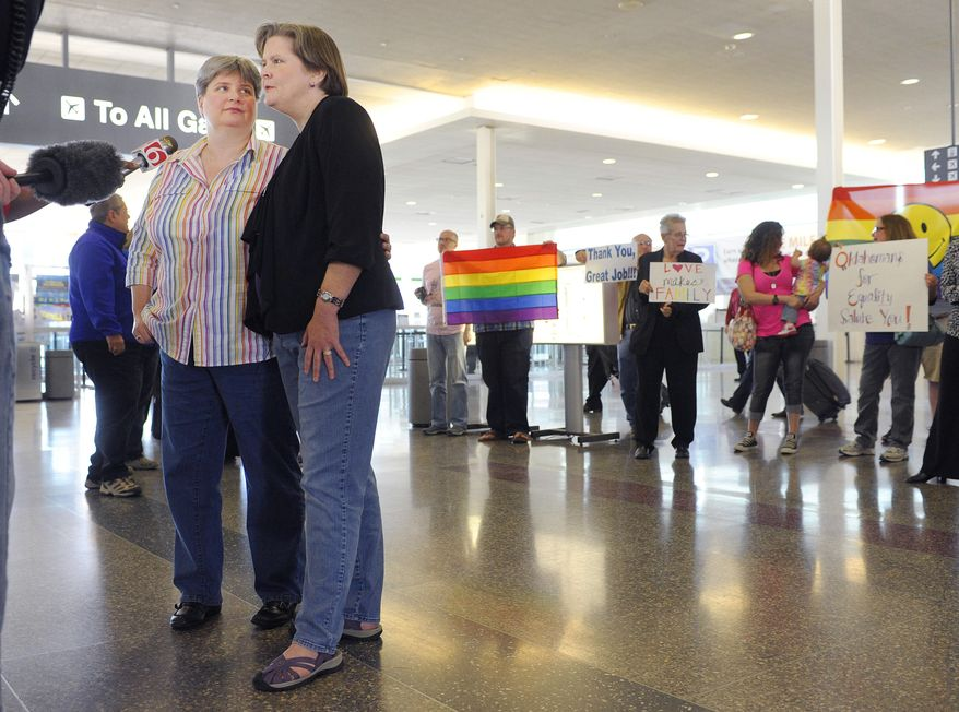 Sharon Baldwin, left, and her partner Mary Bishop speak with members of the media before boarding a plane to Denver at Tulsa International Airport, Wednesday, April 16, 2014. Oklahomans for Equality gathered at Tulsa International Airport with their signs for a send off celebration in support for the plaintiffs, including Baldwin and Bishop, in the Oklahoma Marriage Equality lawsuit as they head to the 10th Circuit Court of Appeals in Denver. (AP Photo/Brandi Simons)