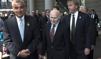Milwaukee Bucks owner Herb Kohl walks into a news conference after reaching a deal to sell the franchise to New York investment firm executives Marc Lasry, right, and Wesley Edens, left, Wednesday, April 16, 2014, in Milwaukee. (AP Photo/Morry Gash)
