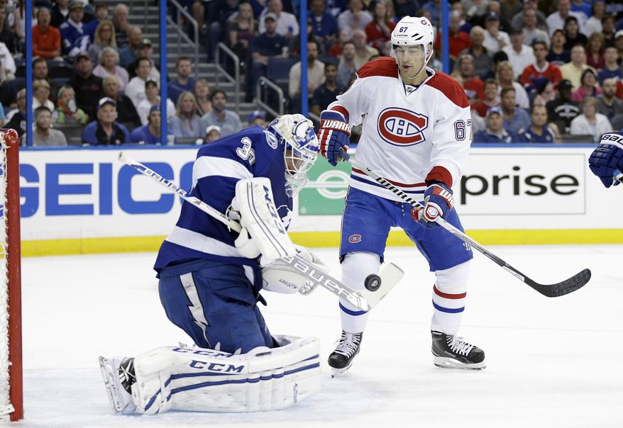 Tampa Bay Lightning goalie Anders Lindback (39), of Sweden, makes a stick-save as Montreal Canadiens left wing Max Pacioretty (67) looks for a rebound on a shot during the first period of Game 1 of a first-round NHL hockey playoff series on Wednesday, April 16, 2014, in Tampa, Fla. (AP Photo/Chris O'Meara)