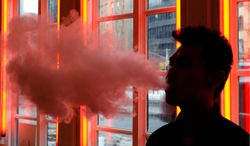 """In this Feb. 20, 2014, photo, a patron exhales vapor from an e-cigarette at the Henley Vaporium in New York. the proprietors are peddling e-cigarettes to """"vapers"""" in a growing movement that now includes celebrity fans and YouTube gurus, online forums and vapefests around the world. (AP Photo/Frank Franklin II)"""