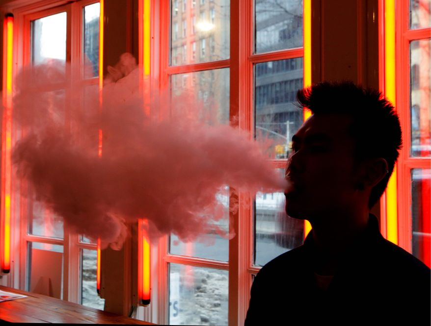 "In this Feb. 20, 2014, photo, a patron exhales vapor from an e-cigarette at the Henley Vaporium in New York. the proprietors are peddling e-cigarettes to ""vapers"" in a growing movement that now includes celebrity fans and YouTube gurus, online forums and vapefests around the world. (AP Photo/Frank Franklin II)"