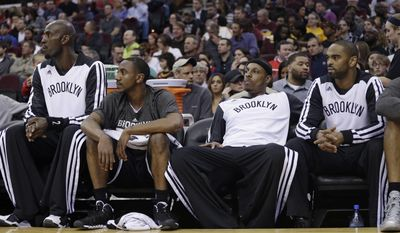 Brooklyn Nets' Kevin Garnett, Marquis Teague, Paul Pierce and Alan Anderson, from left, watch from the bench in the first quarter of an NBA basketball game against the Cleveland Cavaliers on Wednesday, April 16, 2014, in Cleveland. (AP Photo/Tony Dejak)