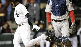Chicago White Sox's Alexei Ramirez celebrates after scoring the game winning run off a throwing error by Boston Red Sox shortstop Xander Bogaerts as A.J. Pierzynski watches during the ninth inning of a baseball game Tuesday, April 15, 2014, in Chicago. The White Sox won 2-1. (AP Photo/Charles Rex Arbogast)