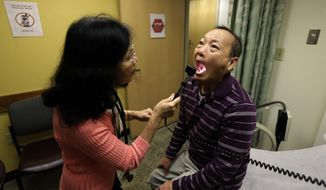 FILE - In this Friday, March 1, 2013 file photo, Chan Lai Ly, right, has his mouth examined by Honghue Duong, a physician's assistant, as part of a regular check-up related to his diabetes at International Community Health Services in Seattle. Over the last two decades, the rates of heart attacks and strokes among diabetics fell by more than 60 percent, a new federal study shows. The research from the Centers for Disease Control and Prevention was reported in the Thursday, April 17, 2014 edition of the New England Journal of Medicine. The drop is mainly attributed to better screening, medicines and care. The improvements came even as the number of U.S. adults with diabetes more than tripled in those 20 years. (AP Photo/Ted S. Warren)