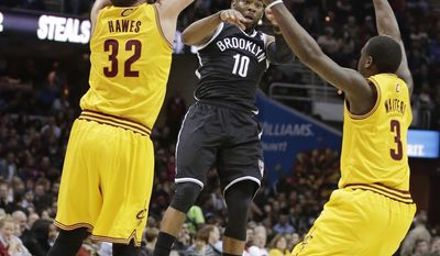 Brooklyn Nets' Marcus Thornton (10) passes over Cleveland Cavaliers' Spencer Hawes (32) and Dion Waiters (3) during the first quarter of an NBA basketball game Wednesday, April 16, 2014, in Cleveland. (AP Photo/Tony Dejak)