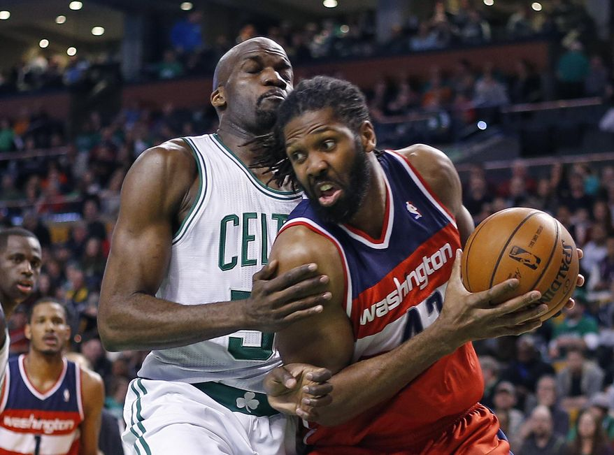 Washington Wizards forward Nene Hilario, right, drives against Boston Celtics center Joel Anthony during the first quarter of an NBA basketball game in Boston, Wednesday, April 16, 2014. (AP Photo/Elise Amendola)
