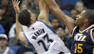 Utah Jazz center Derrick Favors (15) swats away a shot-attempt by Minnesota Timberwolves guard Kevin Martin (23) during the second quarter of an NBA basketball game in Minneapolis, Wednesday, April 16, 2014. (AP Photo/Ann Heisenfelt)