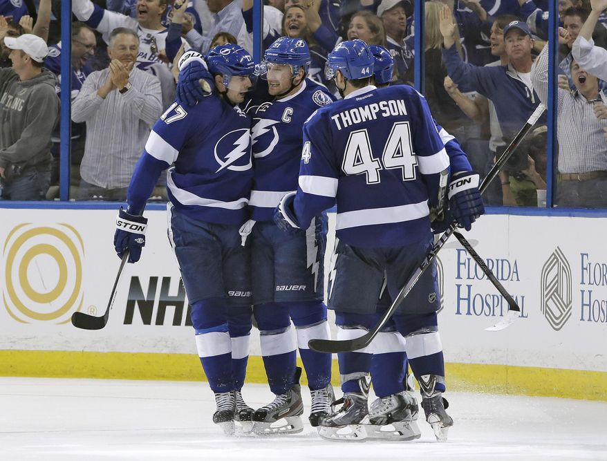Tampa Bay Lightning center Steven Stamkos (91) celebrates with teammates Alex Killorn (17) and Nate Thompson (44) after scoring against the Montreal Canadiens during the third period of Game 1 of a first-round NHL hockey playoff series on Wednesday, April 16, 2014, in Tampa, Fla. (AP Photo/Chris O'Meara)