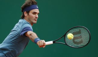 Roger Federer of Switzerland, returns the ball to Radek Stepanek of the Czech Republic during their match of the Monte Carlo Tennis Masters tournament in Monaco, Wednesday, April 16, 2014. (AP Photo/Michel Euler)