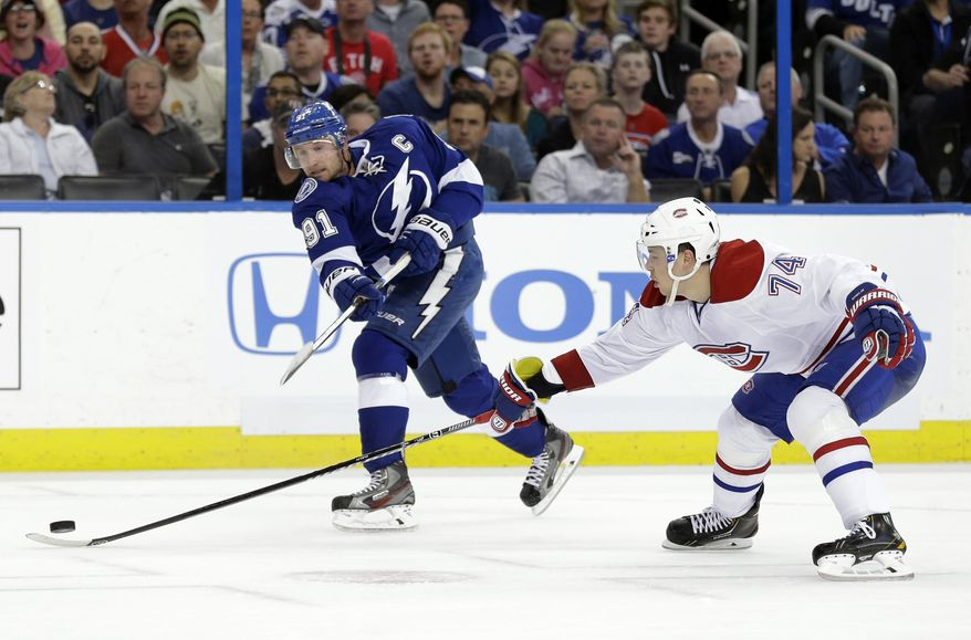 Tampa Bay Lightning center Steven Stamkos (91) fires the puck past Montreal Canadiens defenseman Alexei Emelin (74), of Russia, for a goal during the second period of Game 1 of a first-round NHL hockey playoff series on Wednesday, April 16, 2014, in Tampa, Fla. (AP Photo/Chris O'Meara)