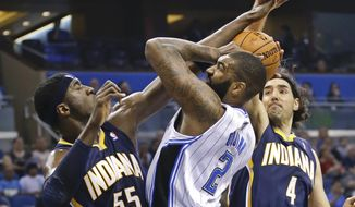 Indiana Pacers' Roy Hibbert (55) ties up the ball as Orlando Magic's Kyle O'Quinn (2) attempts a shot with Luis Scola (4) coming in to help defend during the first half of an NBA basketball game in Orlando, Fla., Wednesday, April 16, 2014. (AP Photo/John Raoux)