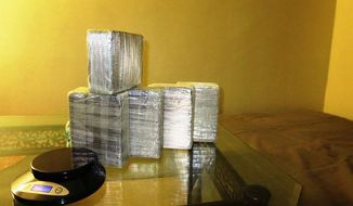 In this April 14, 2014 photo provided by the Office of the Special Narcotics Prosecutor for the City of New York, five kilograms of heroin found between a mattress and box spring of a bed in a New York City apartment is shown during a raid by Drug Enforcement Administration agents. Three men were arrested in the major drug bust that recovered more than $12 million in heroin and $500,000 in crystal meth from inside hidden compartments within two New York City apartments. (AP Photo/Office of the Special Narcotics Prosecutor for the City of New York)