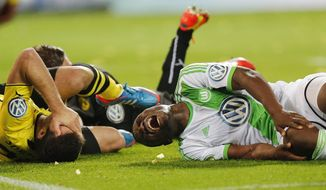 10ThingstoSeeSports - Dortmund's Sokratis, left, and Wolfsburg's Bernard Malanda-Adje lie injured on the pitch during the German soccer cup (DFB Pokal) semifinal match between BvB Borussia Dortmund and VfL Wolfsburg Tuesday, April 15, 2014, in Dortmund, Germany. (AP Photo/Frank Augstein, File)