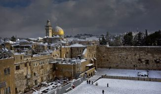 ** FILE ** In this Dec. 13, 2013, file photo, the Western Wall, right, and the gilded Dome of the Rock, among the holiest sites for Jews and Muslims, are covered in snow. (AP Photo/Dusan Vranic, File)
