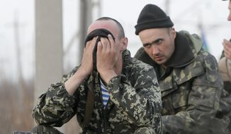 Soldiers of the Ukrainian Army react as they sit a top combat vehicles as they are blocked by people on their way to the town of Kramatorsk on Wednesday, April 16, 2014. The central government has so far been unable to rein in the insurgents, who it says are being stirred up by paid operatives from Russia and have seized numerous government facilities in at least nine eastern cities to press their demands for broader autonomy and closer ties with Russia. (AP Photo/Efrem Lukatsky)