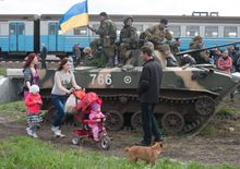 People walk past an Ukrainian Army combat vehicle parked near a railway in Kramatorsk, Ukraine, Wednesday, April 16, 2014. The central government has so far been unable to rein in the insurgents, who it says are being stirred up by paid operatives from Russia and have seized numerous government facilities in at least nine eastern cities to press their demands for broader autonomy and closer ties with Russia. (AP Photo/ Evgeniy Maloletka)