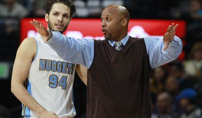 Denver Nuggets head coach Brian Shaw, right, confers with guard Evan Fournier, of France, during a time out against the Golden State Warriors in the third quarter of the Warriors' 116-112 victory in an NBA basketball game in Denver on Wednesday, April 16, 2014. (AP Photo/David Zalubowski)
