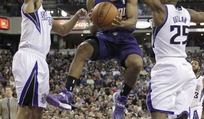 Phoenix Suns guard Ish Smith, center, drives to the basket between Sacramento Kings' Ray McCallum, left, and Travis Outlaw during the first quarter of an NBA basketball game in Sacramento, Calif., Wednesday, April 16, 2014. (AP Photo/Rich Pedroncelli)