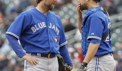 Toronto Blue Jays starting pitcher R.A. Dickey, left, talks with catcher Josh Thole, right, before being replaced by pitcher Todd Redmond during the fifth inning of the first baseball game of a doubleheader against the Minnesota Twins in Minneapolis, Thursday, April 17, 2014.  (AP Photo/Ann Heisenfelt)