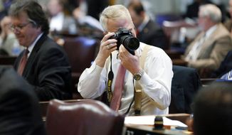 Rep. Jon Lundberg, R-Bristol, takes photographs from his seat in the House of Representatives on the final day of the 108th General Assembly on Thursday, April 17, 2014, in Nashville, Tenn. (AP Photo/Mark Humphrey)