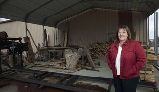 In this March 27, 2014 photo, Grace Curry, of Macon, Ill., stands in front of Curry Sawmill in Boody, Ill., which was the brainchild of her husband before he died in 2010. Curry is in the process of deciding what to do with the business. (AP Photo/Herald & Review, Danny Damiani)