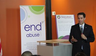 Wisconsin Gov. Scott Walker speaks to supporters of domestic-violence victims on Wednesday, April 16, 2014, in Milwaukee, just before signing three bills aimed at strengthening domestic-violence laws. The measures increase police responsibilities when investigating domestic disturbances and also establish a clear, accountable process for seizing an abuser's guns.  (AP Photo/Dinesh Ramde)