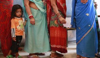 A child holds on to the sari of her grandmother standing in a queue to cast her vote in Rajnandgaon, in the central Indian state of Chhattisgarh, now the center of India's four-decade Maoist insurgency, Thursday, April 17, 2014. Indians cast ballots Thursday on the biggest day of voting in the country's weekslong general election, streaming into polling stations even in areas where rebels threatened violence over the plight of India's marginalized and poor. The state of Chhattisgarh itself was formed only in 2000, carved from its western neighbor Madhya Pradesh based on its large tribal population. (AP Photo/Rafiq Maqbool)