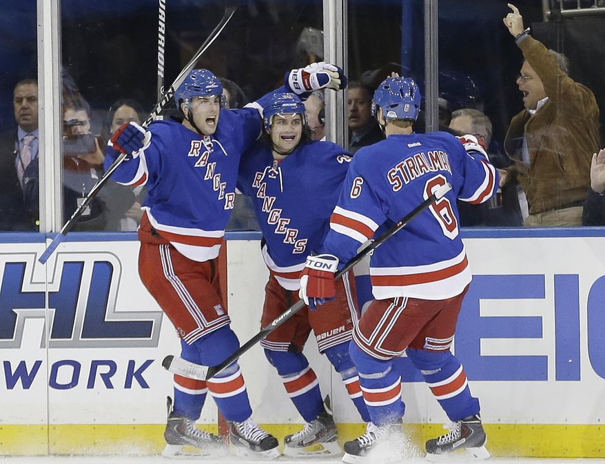 New York Rangers' Derick Brassard, left, and Anton Stralman, right, celebrate with Mats Zuccarello after Zuccarello scored a goal during the first period against the Philadelphia Flyers in Game 1 of an NHL hockey first-round playoff series on Thursday, April 17, 2014, in New York. (AP Photo/Frank Franklin II)
