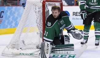FILE - In this April 10, 2014 file photo, North Dakota goalie Zane Gothberg looks for the puck after having his masked knocked off during an NCAA men's college hockey Frozen Four tournament game against Minnesota in Philadelphia. Gothberg, who helped lead North Dakota to the NCAA Frozen Four, announced Wednesday, April 16, 2014, that he would return for his junior season. He was also named the National Collegiate Hockey Conference player of the month for March/April. (AP Photo/Chris Szagola, File)