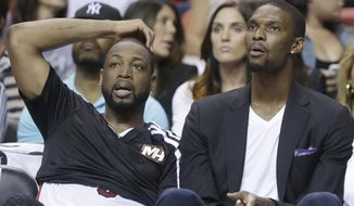 Miami Heat guard Dwyane Wade, left, and center Chris Bosh watch from the bench during the second half of an NBA basketball game against the Philadelphia 76ers, Wednesday, April 16, 2014 in Miami. The 76ers defeated the Heat 100-87. (AP Photo/Wilfredo Lee)