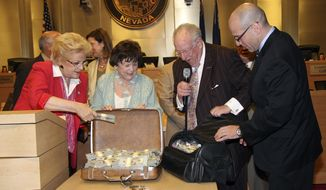 This image provided by the City of Las Vegas shows, from left, Mayor Carolyn G. Goodman, Councilwoman Lois Tarkanian, Oscar B. Goodman and The Mob Museum Executive Director Jonathan Ullman, displaying the $1.5 million in cash donated to the City Council at a meeting on April 16, 2014 in Las vegas. The $100 bills bundled up and stuffed in suitcases are the first of four annual payments the two-year-old museum plans to make to the city.(AP Photo/City of Las Vegas)