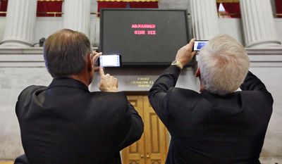 """Rep. Mark Pody, R-Lebanon, left; and Rep. David Alexander, R-Winchester, right; photograph the vote tally board that reads """"Adjourned Sine Die"""" on the final day of the 108th General Assembly on Thursday, April 17, 2014, in Nashville, Tenn. (AP Photo/Mark Humphrey)"""