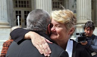 Plaintiff challenging Oklahoma's gay marriage ban Sue Barton, left, gets a hug from her pastor, Tulsa based Reverend Leslie Penrose, of the United Church of Christ, after leaving court following a hearing at the 10th U.S. Circuit Court of Appeals in Denver, Thursday, April 17, 2014. The appeal of a lower court's January ruling that struck down Oklahoma's gay marriage ban is the second time the issue has reached appellate courts since the U.S. Supreme Court shook up the legal landscape last year by finding the federal Defense of Marriage Act was unconstitutional. (AP Photo/Brennan Linsley)